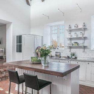 マルメの大きいシャビーシック調のおしゃれなキッチン (木材カウンター、白いキッチンパネル、レンガの床、赤い床、ダブルシンク、シェーカースタイル扉のキャビネット、白いキャビネット、サブウェイタイルのキッチンパネル、茶色いキッチンカウンター) の写真