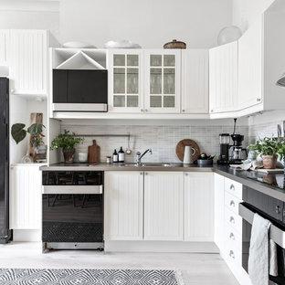 Foto på ett nordiskt grå l-kök, med en dubbel diskho, luckor med lamellpanel, vita skåp, grått stänkskydd, svarta vitvaror, målat trägolv och vitt golv