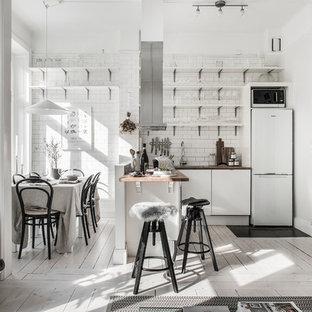 Skandinavisk inredning av ett kök, med öppna hyllor, träbänkskiva, målat trägolv, vitt golv, vita skåp, vitt stänkskydd, stänkskydd i tunnelbanekakel, vita vitvaror och en halv köksö