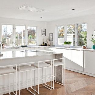 Modern inredning av ett kök, med släta luckor, vita skåp, marmorbänkskiva, ljust trägolv, en köksö och beiget golv