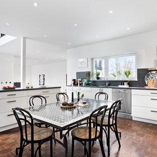 Inredning av ett minimalistiskt mellanstort linjärt kök med öppen planlösning, med släta luckor, vita skåp, en köksö, brunt golv, svart stänkskydd, rostfria vitvaror och mellanmörkt trägolv