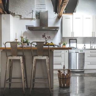 Rustik inredning av ett mellanstort brun brunt kök, med vita skåp, träbänkskiva, vitt stänkskydd, en köksö, skåp i shakerstil, rostfria vitvaror och grått golv