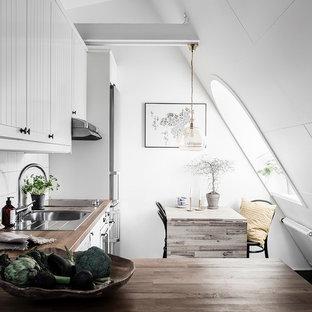 Exempel på ett minimalistiskt brun brunt kök, med en nedsänkt diskho, luckor med lamellpanel, vita skåp, träbänkskiva, vitt stänkskydd och rostfria vitvaror