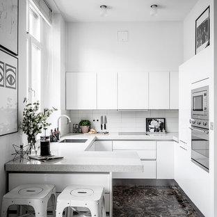 Bild på ett avskilt skandinaviskt grå grått u-kök, med en enkel diskho, släta luckor, vita skåp, vitt stänkskydd, integrerade vitvaror, en halv köksö och brunt golv