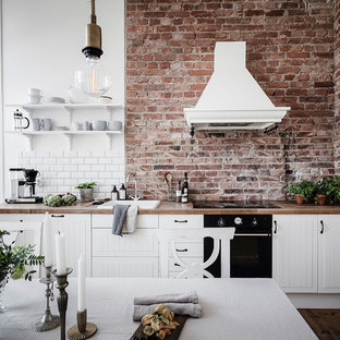 Photo of a mid-sized scandinavian single-wall eat-in kitchen in Gothenburg with white cabinets, wood benchtops, no island, a drop-in sink, louvered cabinets, white splashback, subway tile splashback, black appliances, medium hardwood floors, brown floor and beige benchtop.