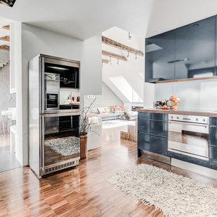 Foto på ett mellanstort funkis linjärt kök med öppen planlösning, med släta luckor, blå skåp, träbänkskiva, grått stänkskydd, glaspanel som stänkskydd, rostfria vitvaror, ljust trägolv, en enkel diskho och brunt golv