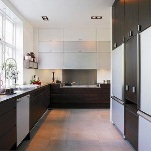 Inredning av ett modernt l-kök, med en enkel diskho, släta luckor, skåp i mörkt trä, stänkskydd med metallisk yta och beiget golv