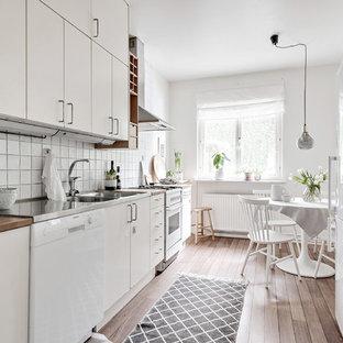 Idéer för ett skandinaviskt kök, med en dubbel diskho, släta luckor, vita skåp, träbänkskiva, vitt stänkskydd, vita vitvaror, mellanmörkt trägolv och brunt golv