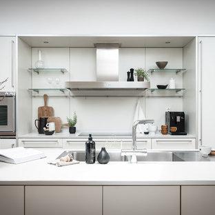 Inredning av ett skandinaviskt vit vitt kök, med en dubbel diskho, släta luckor, vita skåp, vitt stänkskydd, rostfria vitvaror och en köksö