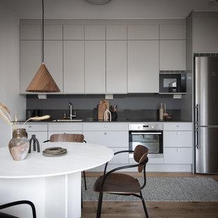 Idéer för att renovera ett skandinaviskt linjärt kök med öppen planlösning, med en integrerad diskho, släta luckor, grå skåp, bänkskiva i rostfritt stål, grått stänkskydd, rostfria vitvaror och mörkt trägolv