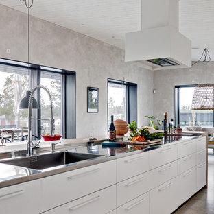 Idéer för ett stort nordiskt kök, med bänkskiva i rostfritt stål, betonggolv, en köksö, en integrerad diskho, släta luckor, vita skåp, integrerade vitvaror och grått golv