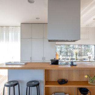 Idéer för ett modernt grå l-kök, med släta luckor, grå skåp, rostfria vitvaror, mellanmörkt trägolv, en köksö och brunt golv