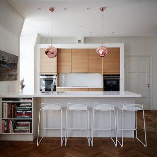 Idéer för funkis linjära kök, med släta luckor, skåp i mellenmörkt trä, vitt stänkskydd, mörkt trägolv och en halv köksö