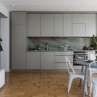 Minimalistisk inredning av ett grå linjärt grått kök med öppen planlösning, med släta luckor, grå skåp, grått stänkskydd, stänkskydd i sten, rostfria vitvaror, mellanmörkt trägolv och brunt golv