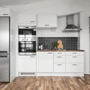 Idéer för att renovera ett mellanstort skandinaviskt linjärt kök med öppen planlösning, med en enkel diskho, släta luckor, vita skåp, träbänkskiva, svart stänkskydd, stänkskydd i keramik, rostfria vitvaror och ljust trägolv