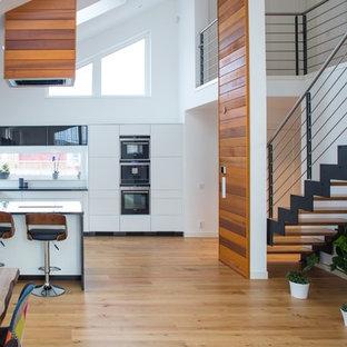 Idéer för ett mellanstort modernt kök, med släta luckor, vita skåp, svarta vitvaror, en halv köksö, en undermonterad diskho, mellanmörkt trägolv och beiget golv