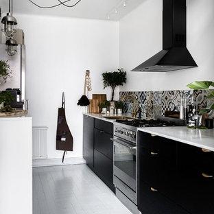 Bild på ett mellanstort skandinaviskt kök, med en undermonterad diskho, släta luckor, svarta skåp, flerfärgad stänkskydd, rostfria vitvaror, målat trägolv och marmorbänkskiva