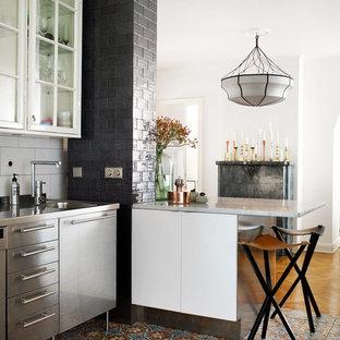 Bild på ett avskilt, mellanstort nordiskt linjärt kök, med en integrerad diskho, luckor med glaspanel, vita skåp, bänkskiva i rostfritt stål, vitt stänkskydd, en halv köksö och klinkergolv i porslin