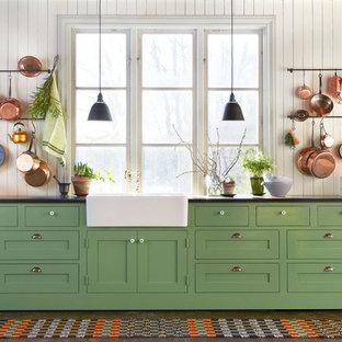 ストックホルムの巨大なカントリー風おしゃれなI型キッチン (エプロンフロントシンク、シェーカースタイル扉のキャビネット、緑のキャビネット、濃色無垢フローリング、ラミネートカウンター、アイランドなし) の写真