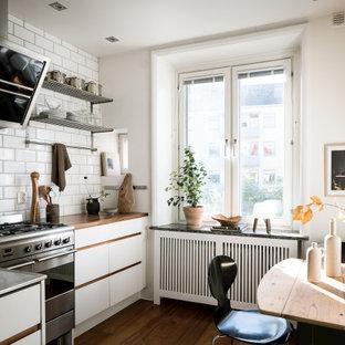 Idéer för ett nordiskt brun kök och matrum, med släta luckor, vita skåp, träbänkskiva, vitt stänkskydd, stänkskydd i tunnelbanekakel, rostfria vitvaror, mörkt trägolv och brunt golv