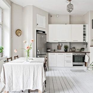 Пример оригинального дизайна: большая линейная кухня в скандинавском стиле с плоскими фасадами, белыми фасадами, столешницей из дерева, серым фартуком, деревянным полом, белым полом, коричневой столешницей, обеденным столом и техникой из нержавеющей стали без острова