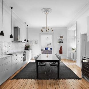 Inredning av ett skandinaviskt stort linjärt kök och matrum, med släta luckor, grå skåp, marmorbänkskiva, grått stänkskydd och stänkskydd i marmor