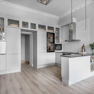 Inspiration för ett stort skandinaviskt svart svart kök, med släta luckor, vita skåp, en halv köksö, en undermonterad diskho, vitt stänkskydd, stänkskydd i tunnelbanekakel, integrerade vitvaror, mellanmörkt trägolv och brunt golv