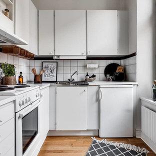 Idéer för att renovera ett avskilt, litet nordiskt l-kök, med en nedsänkt diskho, släta luckor, vita skåp, vitt stänkskydd, vita vitvaror, mellanmörkt trägolv och brunt golv