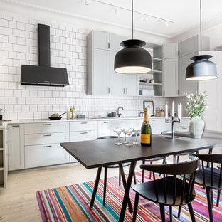 Inspiration för ett stort skandinaviskt kök, med skåp i shakerstil, grå skåp, vitt stänkskydd och ljust trägolv