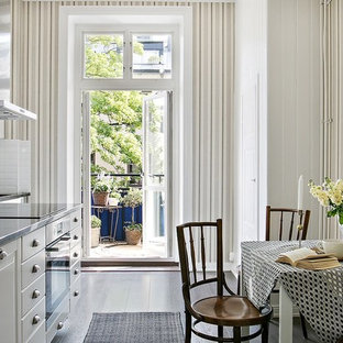 Design ideas for a mid-sized victorian eat-in kitchen in Stockholm with flat-panel cabinets, white cabinets, white splashback, dark hardwood floors, no island and black floor.
