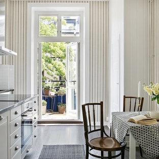 ストックホルムの中サイズのヴィクトリアン調のおしゃれなダイニングキッチン (フラットパネル扉のキャビネット、白いキャビネット、白いキッチンパネル、濃色無垢フローリング、アイランドなし、黒い床) の写真