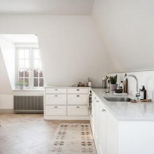 Minimalistisk inredning av ett grå grått kök, med en undermonterad diskho, luckor med infälld panel, vita skåp, mellanmörkt trägolv och brunt golv