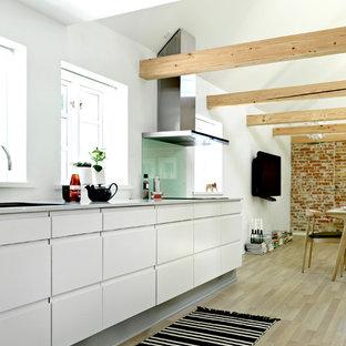 他の地域の中サイズの北欧スタイルのおしゃれなキッチン (ドロップインシンク、フラットパネル扉のキャビネット、白いキャビネット、ラミネートカウンター、白いキッチンパネル、ガラス板のキッチンパネル、淡色無垢フローリング、アイランドなし) の写真