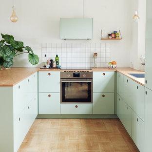 コペンハーゲンの北欧スタイルのおしゃれなペニンシュラキッチン (ドロップインシンク、フラットパネル扉のキャビネット、緑のキャビネット、木材カウンター、白いキッチンパネル、シルバーの調理設備、無垢フローリング) の写真