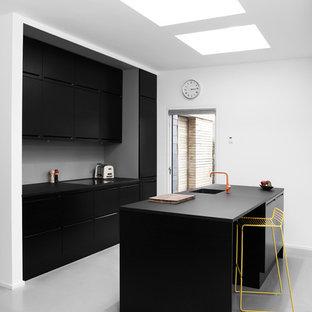 Выдающиеся фото от архитекторов и дизайнеров интерьера: отдельная, параллельная кухня среднего размера в скандинавском стиле с монолитной раковиной, плоскими фасадами, черными фасадами, столешницей из дерева, черной техникой, полом из линолеума и островом