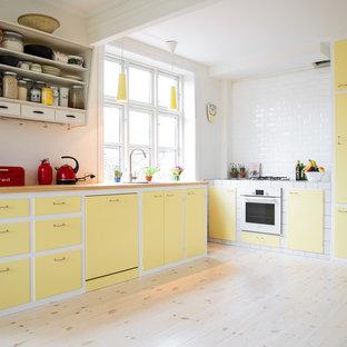 Ejemplo de cocina en L, nórdica, grande, sin isla, con fregadero de un seno, armarios con paneles lisos, puertas de armario amarillas, salpicadero blanco, suelo de madera clara y suelo beige