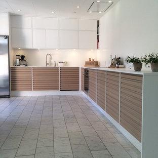 他の地域の大きい北欧スタイルのおしゃれなL型キッチン (中間色木目調キャビネット、白いキッチンパネル、アイランドなし、ルーバー扉のキャビネット、ドロップインシンク、シルバーの調理設備の、グレーの床、白いキッチンカウンター) の写真