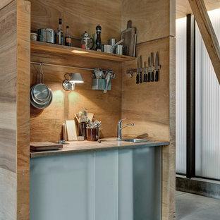 Rustikale Küche mit Waschbecken, offenen Schränken, hellen Holzschränken, Rückwand aus Holz, Betonboden, grauem Boden und grauer Arbeitsplatte in Aalborg