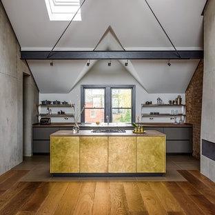 Idéer för att renovera ett industriellt kök, med släta luckor, gula skåp, träbänkskiva, en köksö och brunt golv