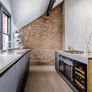 Photo of an industrial galley open plan kitchen in London with flat-panel cabinets, yellow cabinets, wood worktops, an island and brown floors.