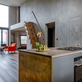Offene, Zweizeilige Industrial Küche mit flächenbündigen Schrankfronten, gelben Schränken, Arbeitsplatte aus Holz, Kücheninsel und braunem Boden in London