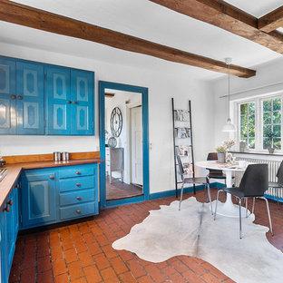 コペンハーゲンの中くらいのカントリー風おしゃれなキッチン (インセット扉のキャビネット、青いキャビネット、木材カウンター、レンガの床、アイランドなし、茶色いキッチンカウンター、ドロップインシンク、白い調理設備、赤い床) の写真