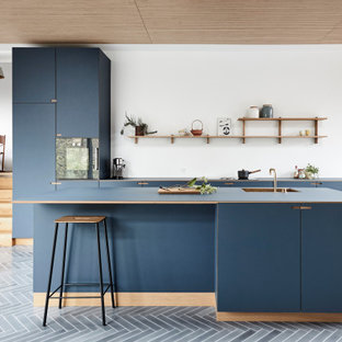 Large contemporary galley open plan kitchen in Copenhagen with flat-panel cabinets, blue cabinets, panelled appliances, with island, grey floor, blue benchtop and cement tiles.