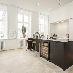 Diseño de cocina de galera, actual, grande, abierta, con fregadero integrado, armarios con paneles lisos, puertas de armario blancas, encimera de laminado, electrodomésticos de acero inoxidable, suelo de madera clara y una isla