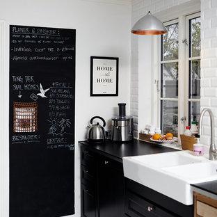 Стильный дизайн: кухня в стиле кантри с раковиной в стиле кантри, фасадами с утопленной филенкой, черными фасадами, белым фартуком, фартуком из плитки кабанчик и деревянным полом - последний тренд