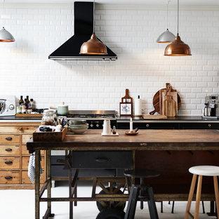 Modelo de cocina de galera, industrial, de tamaño medio, con armarios con paneles lisos, puertas de armario negras, salpicadero blanco, salpicadero de azulejos tipo metro, electrodomésticos negros y una isla