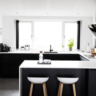 Foto på ett mellanstort minimalistiskt kök, med en undermonterad diskho, svarta skåp, en halv köksö, släta luckor, laminatbänkskiva och klinkergolv i keramik