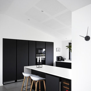Foto di una cucina moderna di medie dimensioni con ante lisce, ante nere, top in laminato, pavimento con piastrelle in ceramica e penisola