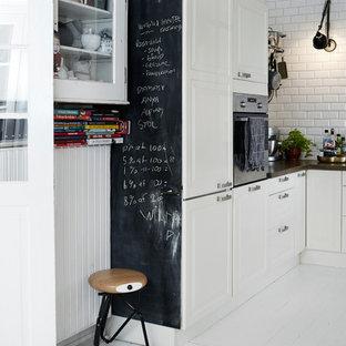 Exempel på ett skandinaviskt kök, med luckor med upphöjd panel, vita skåp, vitt stänkskydd, stänkskydd i tunnelbanekakel och målat trägolv