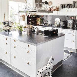 ウィルトシャーの大きいエクレクティックスタイルのおしゃれなアイランドキッチン (フラットパネル扉のキャビネット、白いキャビネット、黒い床、黒いキッチンカウンター) の写真